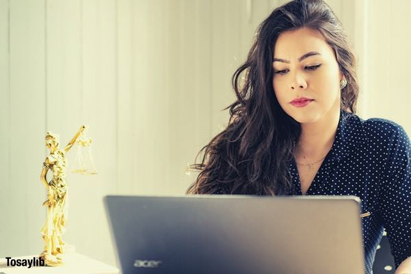 woman wearing black blouse with white polka dots working laptop