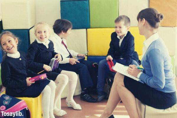 elementary school students and teacher sitting in cube cushion