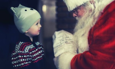 santa-claus-giving-gift-to-a-toddler-wearing-black-sweater