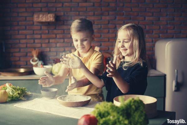 happy children putting flour on hands in kitchen in apartment