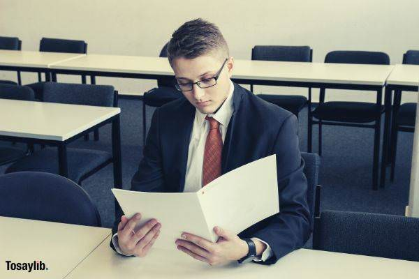 man holding folder reading empty room