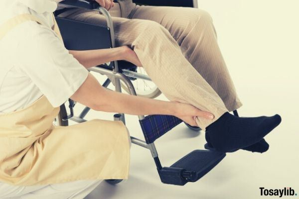 nurse holding the leg of patient putting on wheelchair footrest