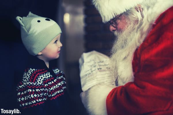 santa claus giving gift to a toddler wearing black sweater