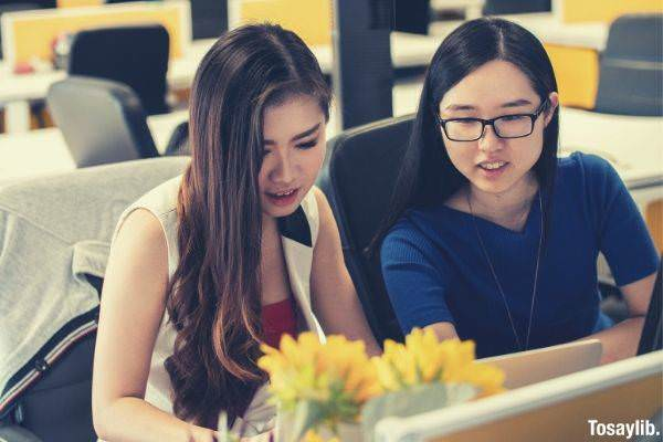 two girls looking at the laptop sleeveless and blue shirt with glasses