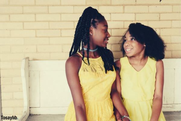 two girls wearing yellow sleeveless dresses looking at each other
