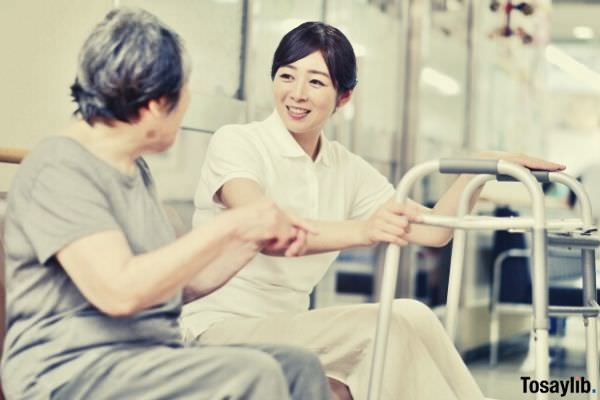 woman talking to old patient holding a gray crane