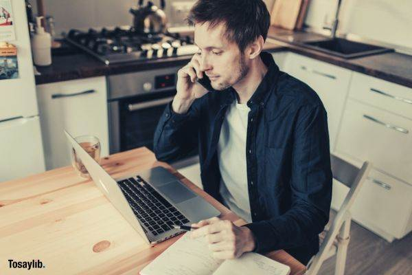 male freelancer making phone call and watching laptop in kitchen