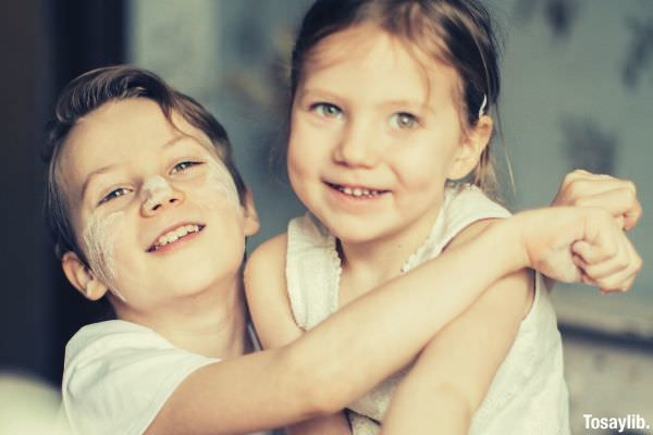 two children sibblings smiling boy hugging the girl