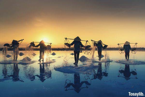 five people walking in body of water carrying baskets wearing sakkat