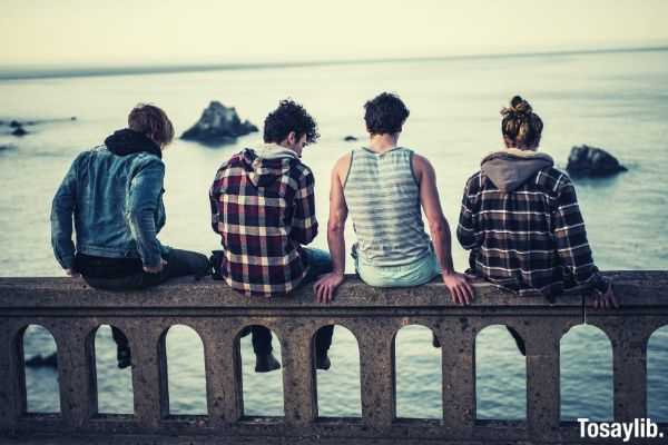 four people friends sitting on the bench in front of body of water
