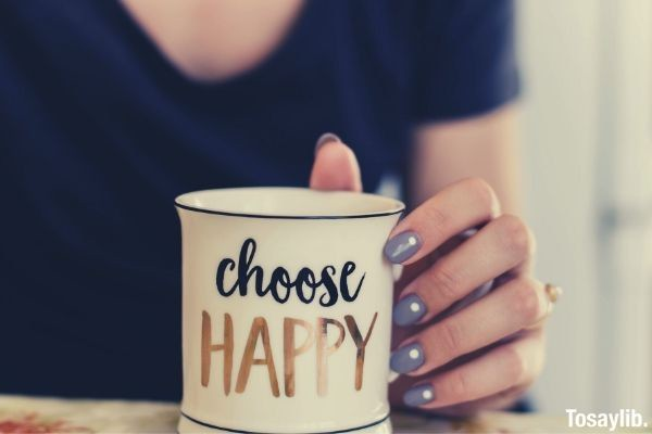 selective focus photography of person touch the white ceramic mug with choose happy graphic nail polish