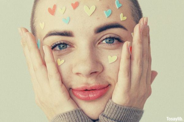 young positive woman with many different colored heart stickers on face bald