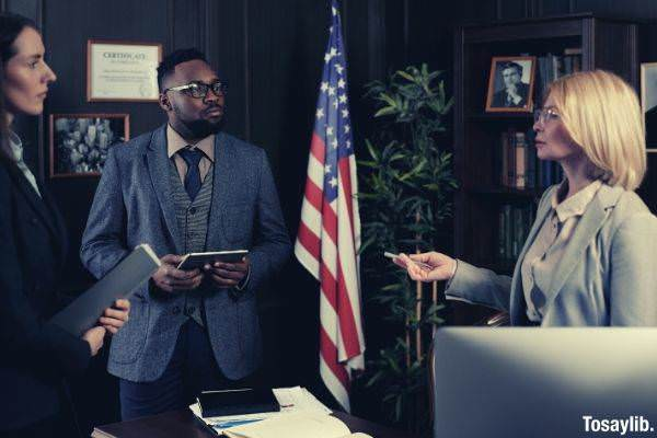 lawyers standing and talking to each other inside the office american flag