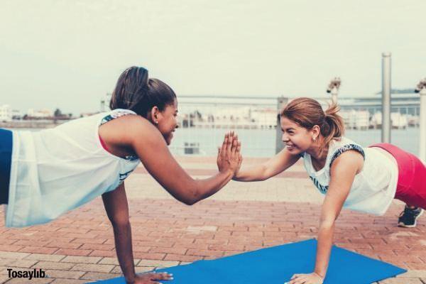 two women doing push up appear blue floor mat outdoor brick type floor