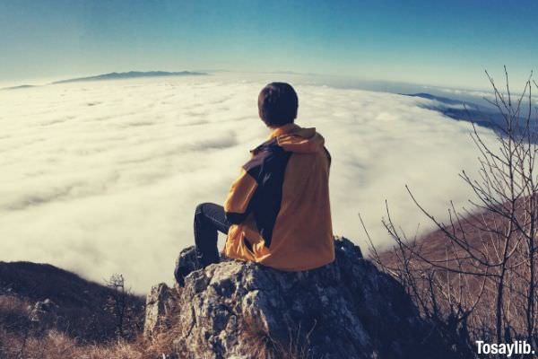 man sitting on the rock looking at the sea of clouds