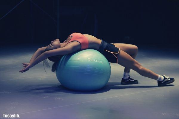 woman doing yoga on blue stability ball dark room pink bra short