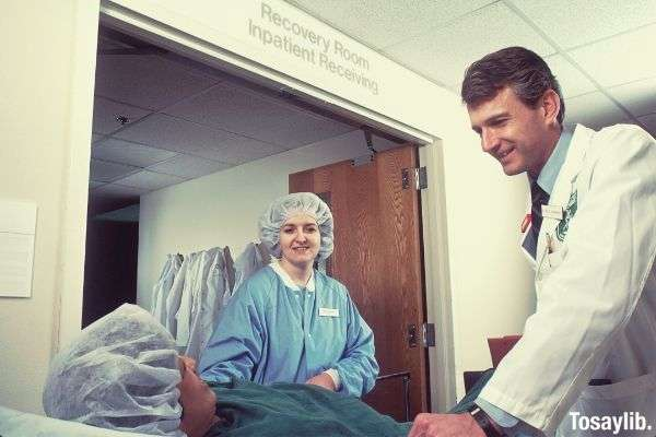 woman in scrub suit and a doctor standing beside the patient