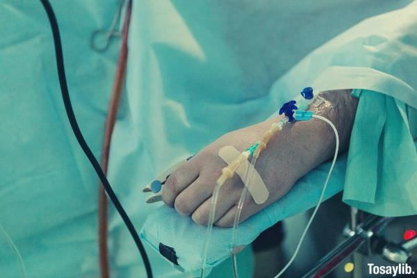man lying in hospital bed dextrose sick resting