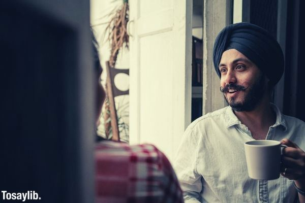 young indian man with turban wearing cup off coffee chatting with wife at home