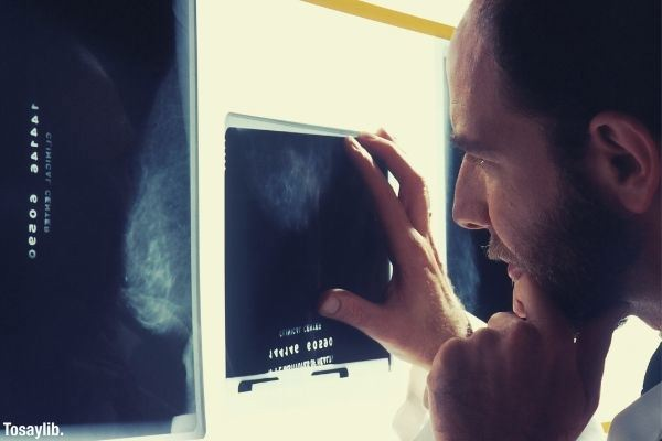 person doctor looking at x ray result touching his beard