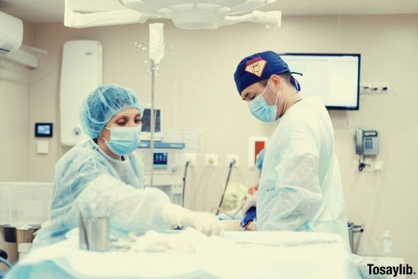 photo of two healthcare professionals inside operating room ultrasound wearing scrubsuits