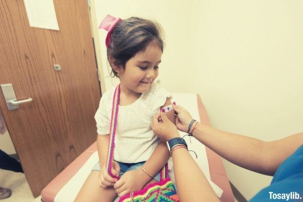 cute girl getting vaccine and doctor putting cute sticker band aid