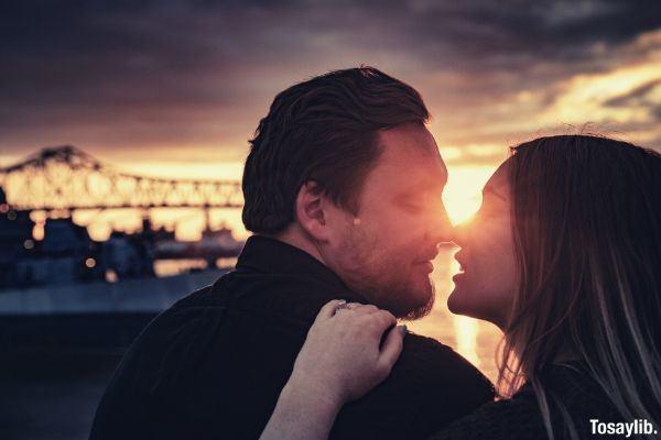man black sweater woman kissing sunset bridge