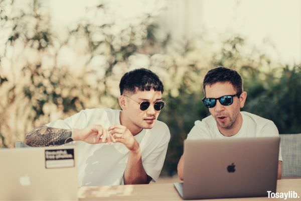 two men wearing white shirt sitting near the table using macbooks