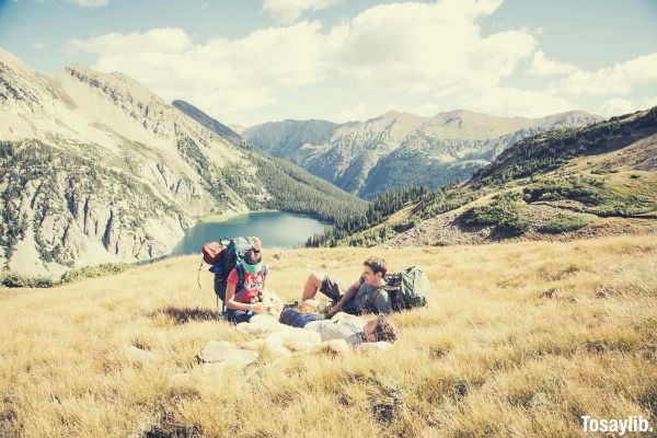 hikers relax on a mountainside meadow in colorado friends lying