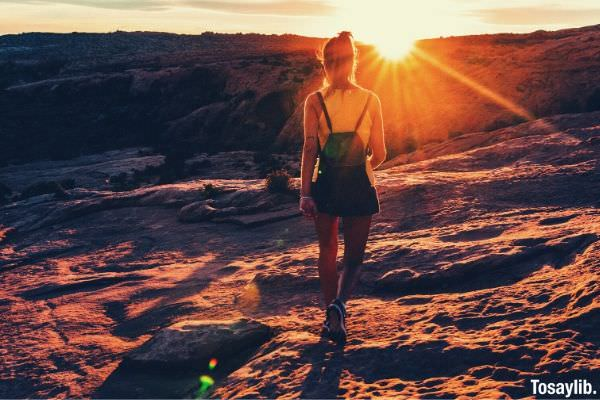 woman in top tank with backpack hiking sunset