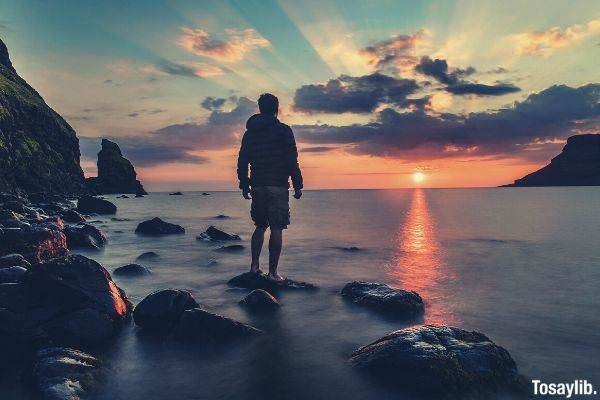 man standing on the rock looking at the sun sunrays clouds water moving