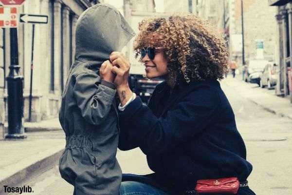 05 woman holding kid at street buildings