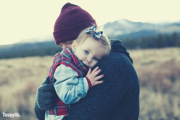 02 father hugging baby girl mountain grass field