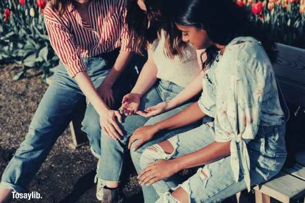 06 girls sitting bench holding hands tattered jeans flowers
