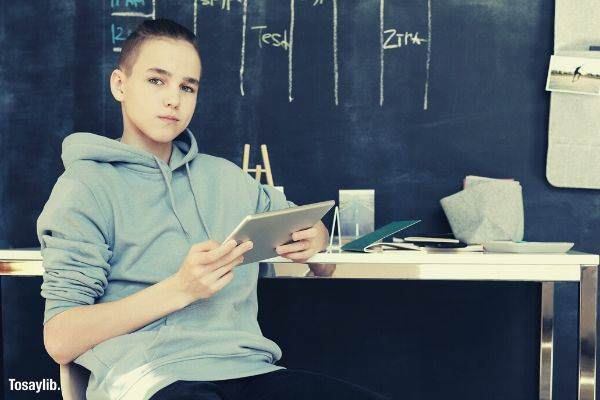 07 boy in gray hoodie and black pants while sitting on chair holding tablet black board