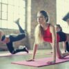 group-of-women-doing-yoga-brick-wall-racing-left-foot-pink-floor-mat