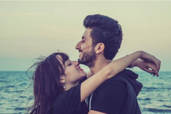man-and-woman-happy-in-black-facing-each-other-on-the-beach