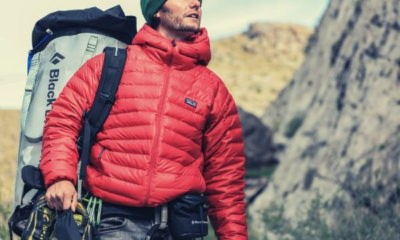 man-hiking-looking-somewhere-holding-his-shoes-backpack-red-jacket