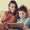 feature-photo-of-woman-and-boy-watching-through-tablet-computer-while-sitting-at-the-sofa