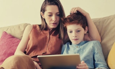 photo-of-woman-and-boy-watching-through-tablet-computer-while-sitting-at-the-sofa