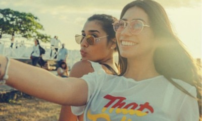 two-women-friends-wearing-sunglasses-taking-a-selfie-of-theirselves-and-sunset