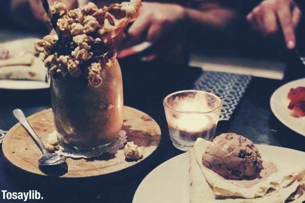 chocolate shake beside ice cream crepe on the table