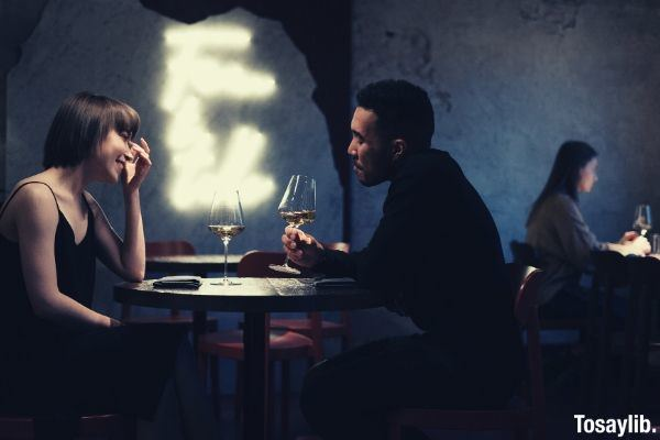 man in black long sleeve shirt sitting on a chair having wine with a lady