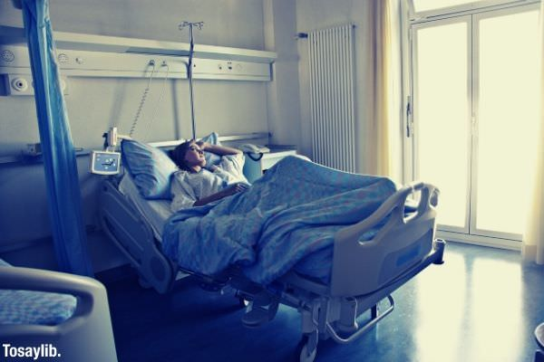woman lying in hospital bed sick getting well