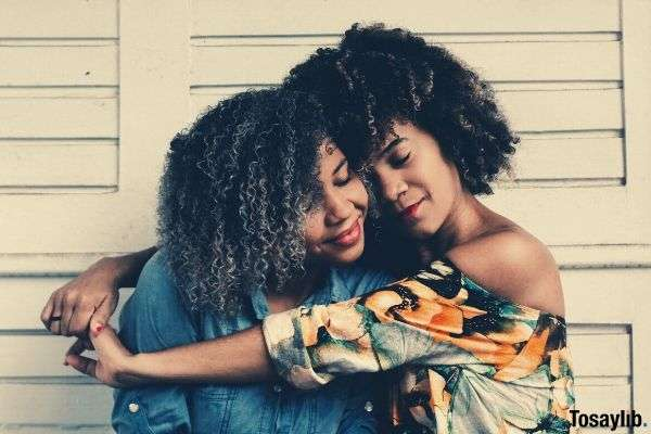 woman with curly hair wearing off shoulder clothes hugging another woman