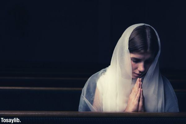 woman with white scarf praying black background