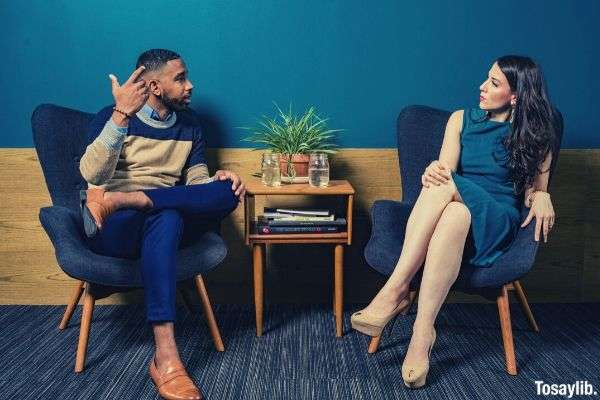 woman wearing teal dress sitting on chair talking to man in semi formal clothes