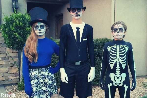 kids wearing halloween costumes outside the house girl on blue boy on black and another boy in skeleton