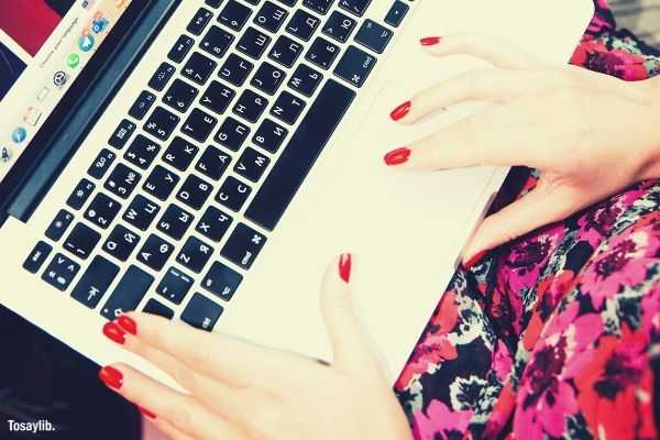 woman using macbook floral dress hands with red nail polish