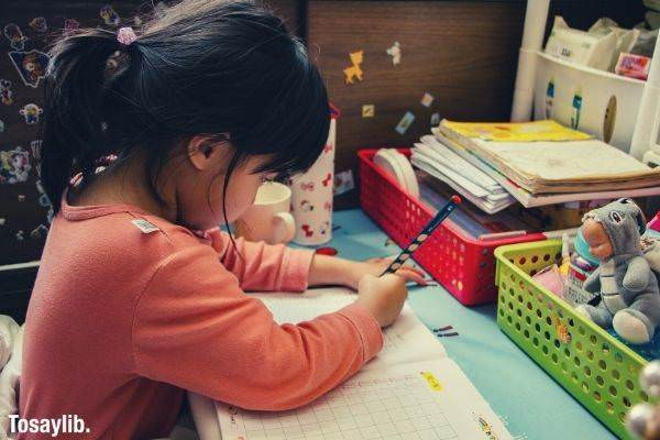 Girl in orange long sleeves writing on a work book on her study table